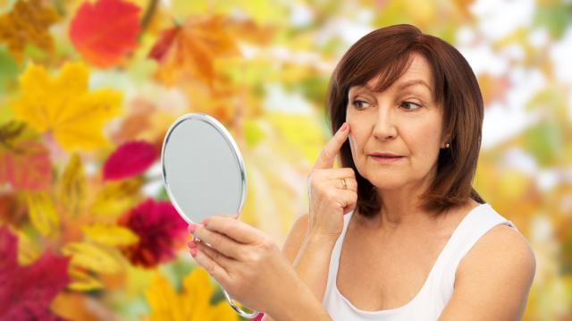 摄图网_300065222_秋天户外照镜子触摸脸颊的中年妇女(非企业商用).jpg